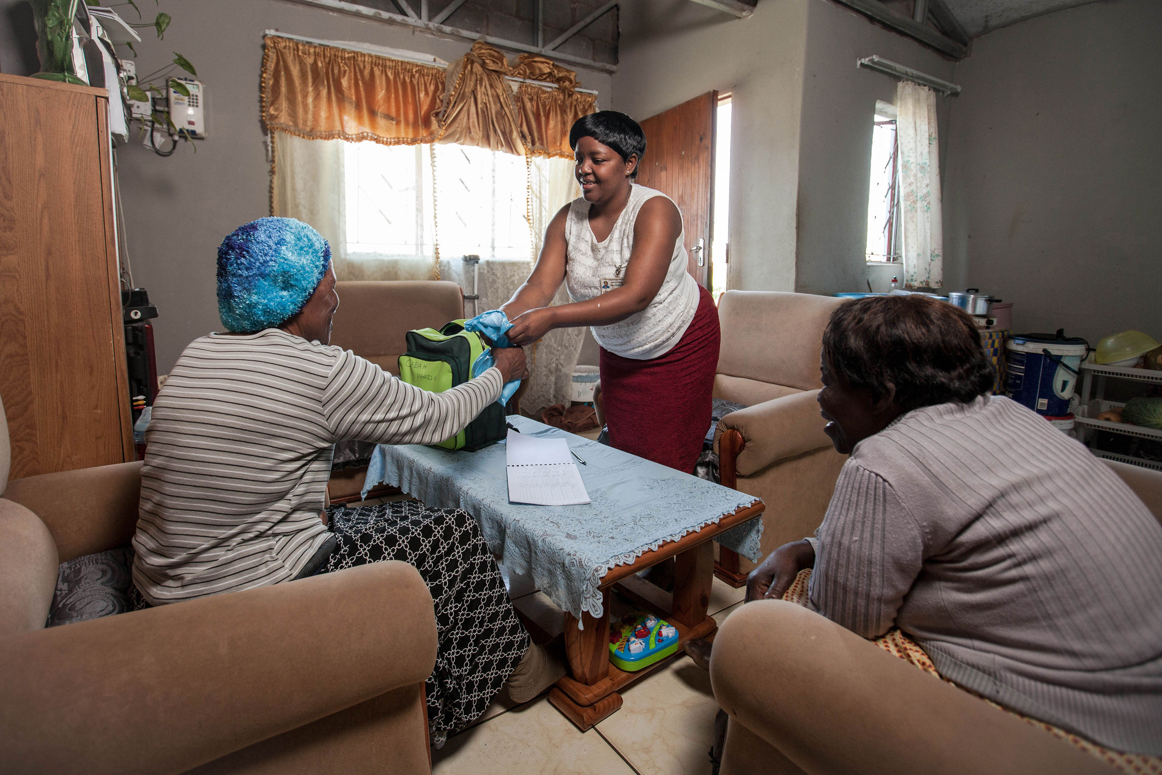 "MSF has been piloting ""Community Anti-Retroviral Treatment Groups"" (CAGs) as a model of care for stable HIV+ patients in rural districts of southern Africa, where HIV prevalence is at its highest. Community Care Giver Nonhlanhla Ngema delivers anti-retrovirals to Elizabeth."