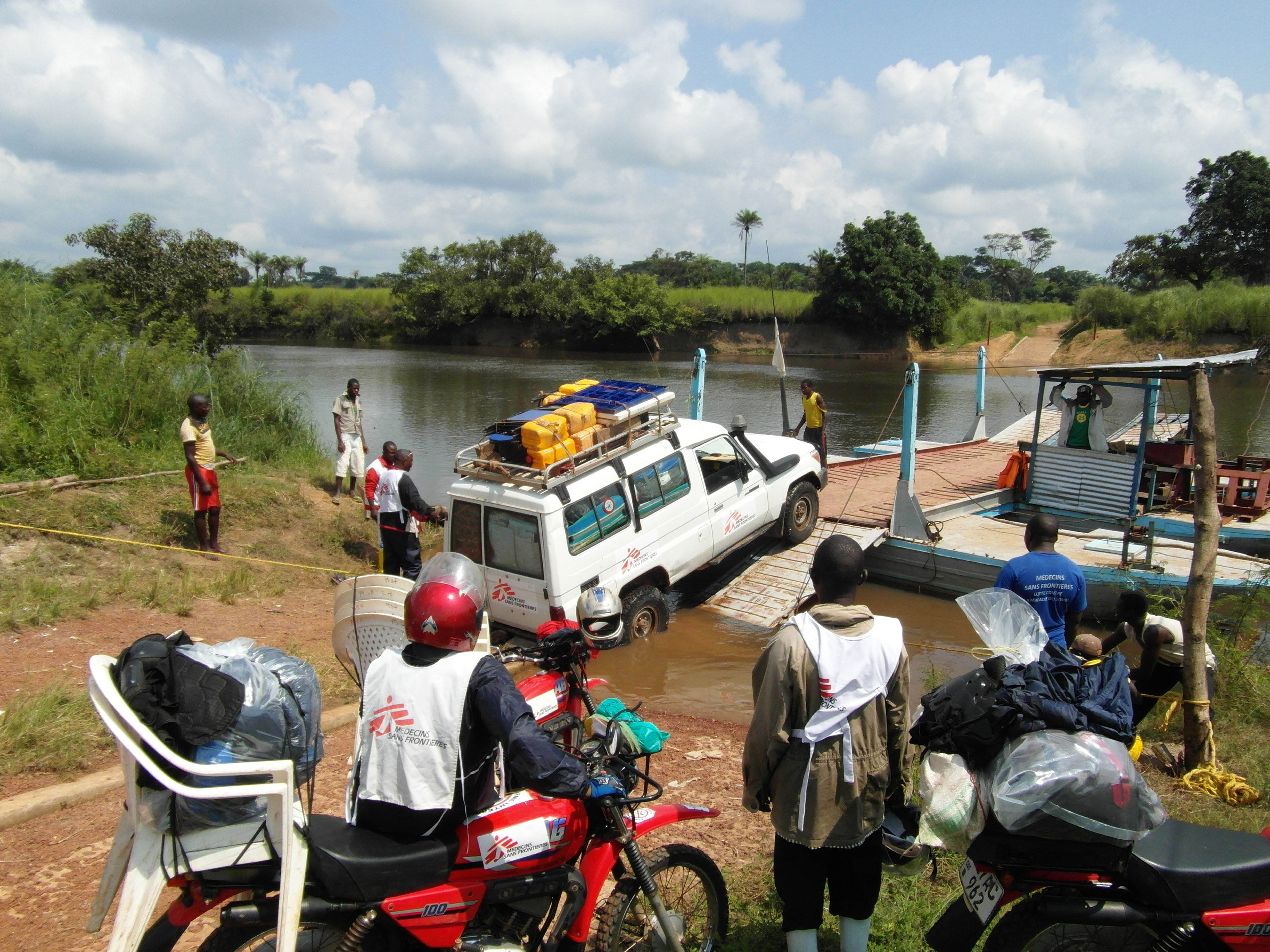 MSF mobile medical team crosses the river with cars and motorbikes to reach remote villages.