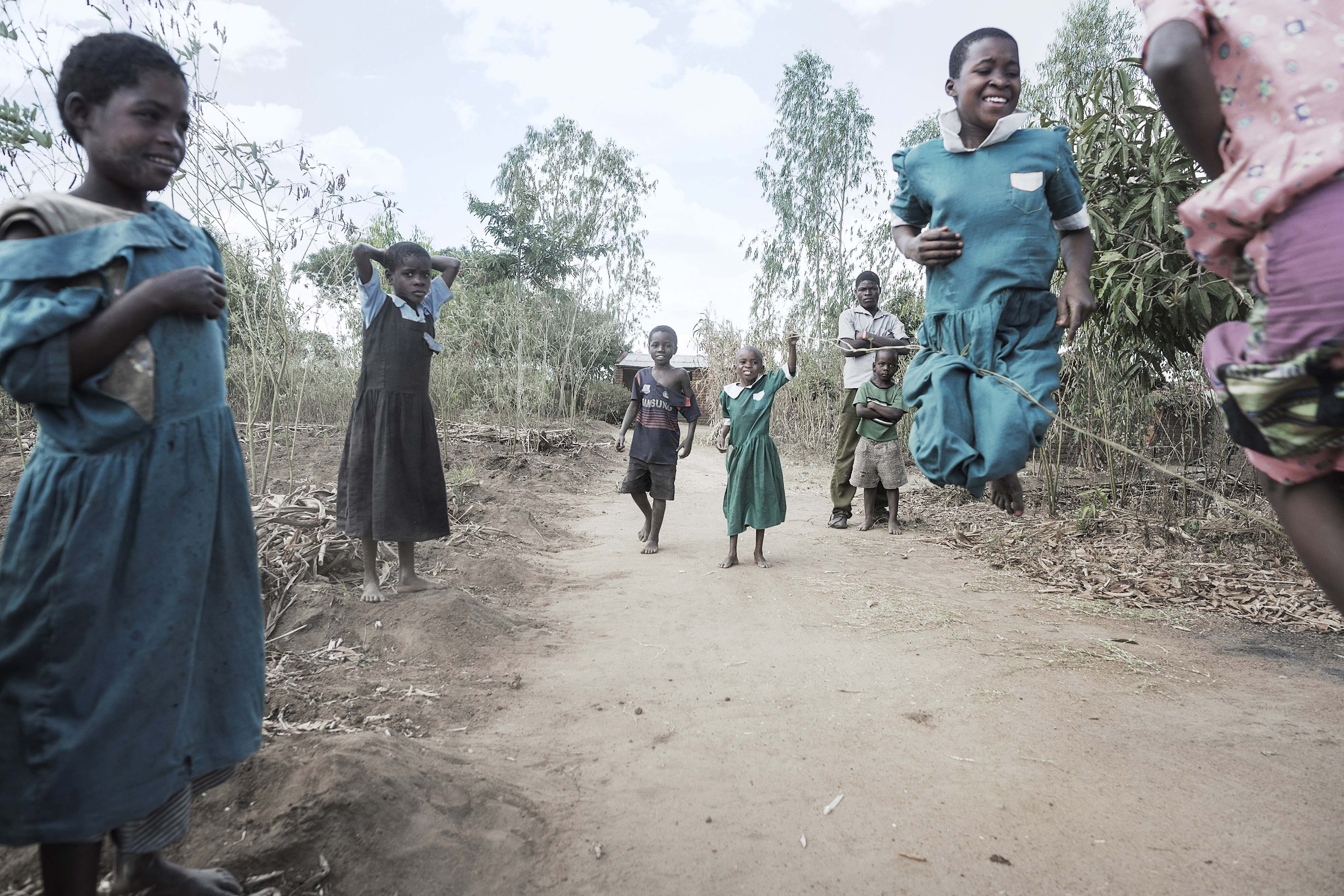 Gloria Chipasula, 11 years old MSF's HIV and TB positive patient stands in in the middle of the road (green dressed) as she plays with her young relatives and village's friends.