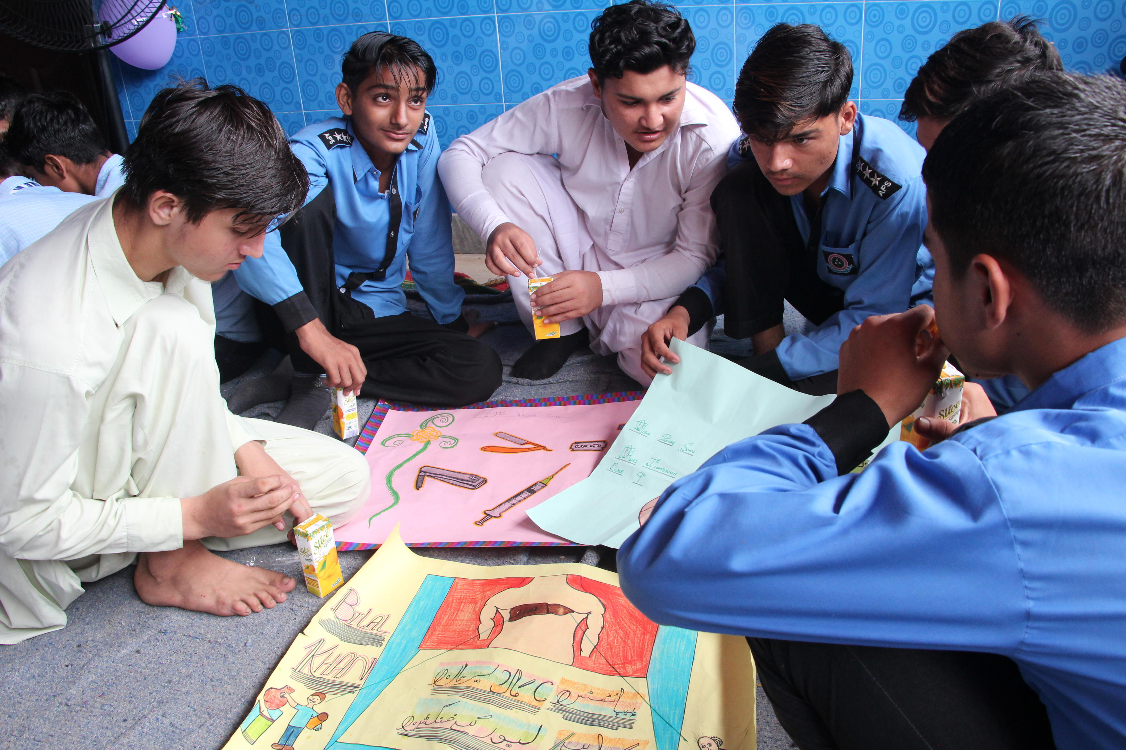 A local youth peer group discuss final changes to their posters for the world hepatitis day celebrations.