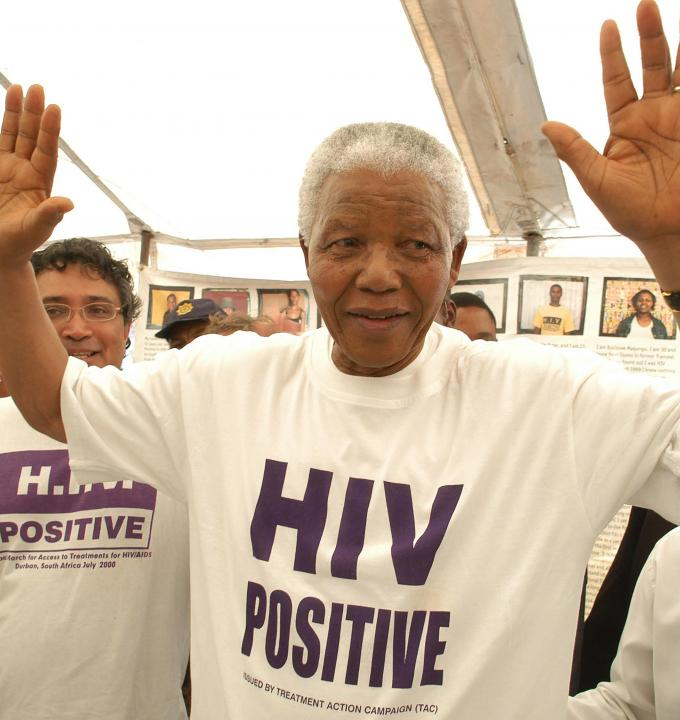 Former South African president Nelson Mandela has accepted the offer of a beneficiary of the project and has changed his shirt for an HIV-Positive T-shirt. See Zackie (Zackie Achmat of the Treatment Action Campaign, a South African NGO {TAC}) just behind.