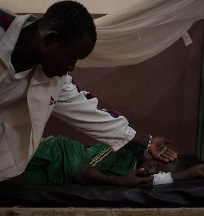 Nicsonne Dadjam, 13, is treated at Paoua Hospital, northwestern Central African Republic, supported by MSF. He was bitten by a snake while working in the fields in his village, 2 hours by motorbike from Paoua. His older brother is checking his temperature, 2018.