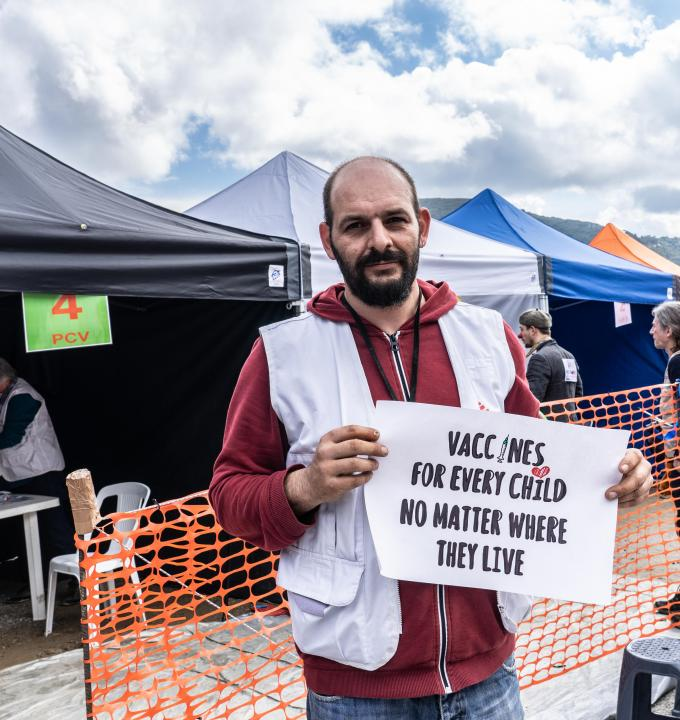 MSF logistician, Athanasios Papadopoulos holding a sign advocating for broader use of the pneumonia vaccine at a lower price