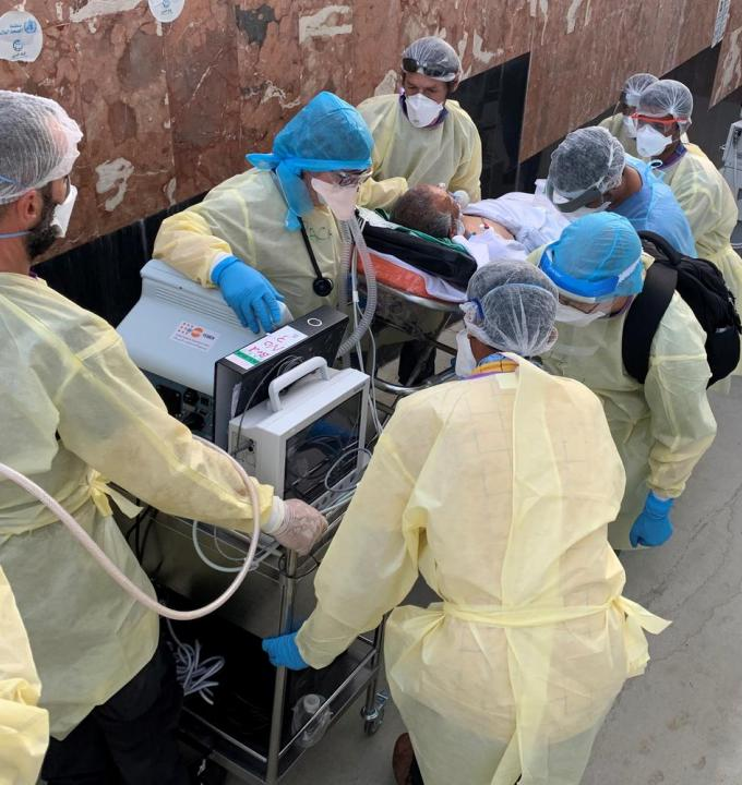 An MSF team of doctors, nurses, logisticians and biomedical technicians painstakingly move a patient seriously-ill with COVID-19 during their transfer to a new purpose-built intensive care unit at our COVID-19 treatment centre in Aden.
