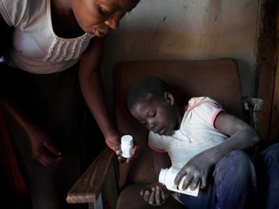 Ten year old Tanya, who is HIV positive and unable to walk, takes her medication with the help of her neighbor Florence who she calls 'Mama'. Her mother died in 2010. Florence, Tanya and her mother we all part of the first group of patients to join MSF and the Ministry of Health and Childcare's Epworth HIV program a decade ago, 28 October 2016.