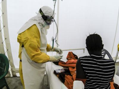 National staff members dressed in PPE attend to a 16 year old girl confirmed with Ebola, in Sierra Leone, 2015
