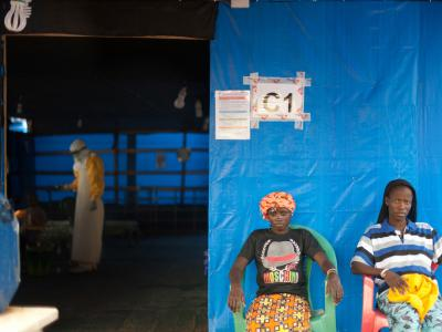 In the MSF Ebola Treatment Center in Guéckédou, Finda (left), and Kadia (right), two Ebola patients participating in the favipiravir trial, relax outside their ward. Inside, MSF staff care for a five year old boy whose mother died from Ebola the previous day.