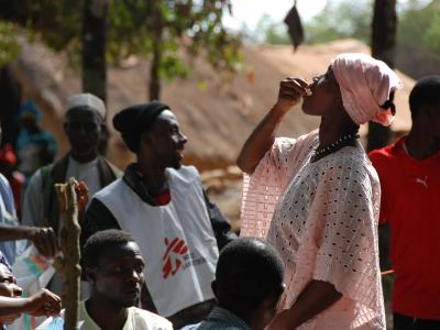 Woman drinking the first dose of the first oral vaccine against cholera in Africa during an epidemic, Guinea, Tougnifili/Mankountan, 2012