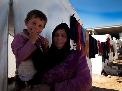A Syrian displaced woman, Saleha Mustafa, and her young child in a transit camp next to the Turkish border.