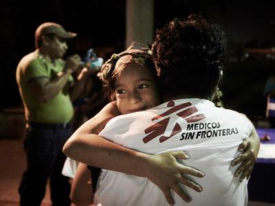 MSF social worker hugs a migrant girl
