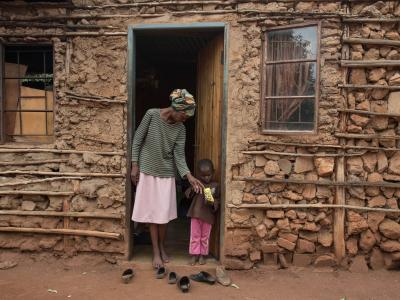 Winile stands outside her house in the Manzini region of Swaziland