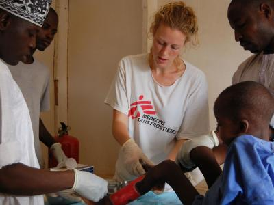 Paediatric nurse Claire Hudson (centre) and MSF nurse Mutola (right), with the help of a MoH nurse (in the hat), dress 7 year old Kabiru's wound from a suspected snake bite in Goronyo, Nigeria, 2017.