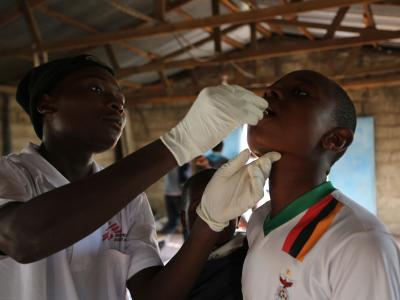 A member of the MSF vaccination team provides a single dose of oral cholera vaccine to a boy at True Vine Church, one of the 15 sites used by MSF in the district of Kanyama during a massive vaccination campaign in Lusaka