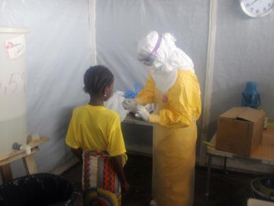 A nurse gives pain killers to a 12-years old girl staying in the Ebola isolation ward.