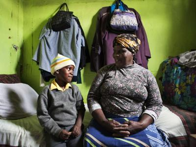Thenjiwe Madzinga, 66, sits on with her grandson Thina Gxotelwa in the small room they share in a shack in Cape Town's Khayelitsha township, February 23, 2010. Madzinga cares for her five grandchildren, including four who were orphaned when Madzinga's own daughter died from AIDS in 2002. Some 5.5 million people live with HIV/AIDS in South Africa - more than in any other country - placing a heavy burden on a society still struggling with the legacy of Apartheid.