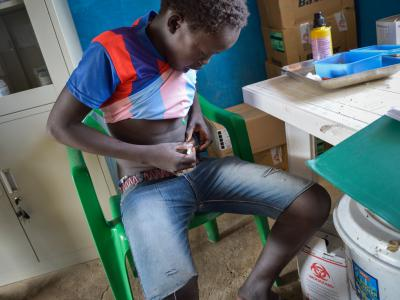 14-year-old Deng Gwin administering his own insulin injection as per instructions in MSF's diabetes clinic in Agok hospital. His dreams of becoming a famous footballer have been set back by his illness, but he is feeling better with treatment